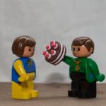 Auf dem Bild sind 2 Duplo-Figuren. Er möchte ihr einen Schwarzwäldertorte anwerfen.