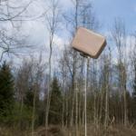 Ein fliegender Koffer der nur von einem Seil festgehalten wird. Im Hintergrund ist ein Wald.