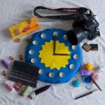 In der Mitte ist eine blaue Uhr mit Sonne. Rundherum im Urzeigersinn angeordnet: Eine Kamera mit zwei Speicherkarten, Häkelnadeln mit Wolle und fertigen Häkeltierchen, Stoff mit Ziernähten und Nähutensilien (Faden, Nadeln, Kreidestift und Stoffklammern), Schokolade und Karamellbonbons.