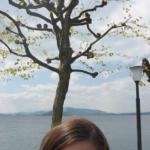 Vorne in der Mitte ist der obere Teil meines Kopfes zu sehen. Hinter mir stehen drei Bäume und ein Laternenpfahl. Im Hintergrund ist noch der Zugersee, die hüglige Landschaft und der bewölkte Himmel.