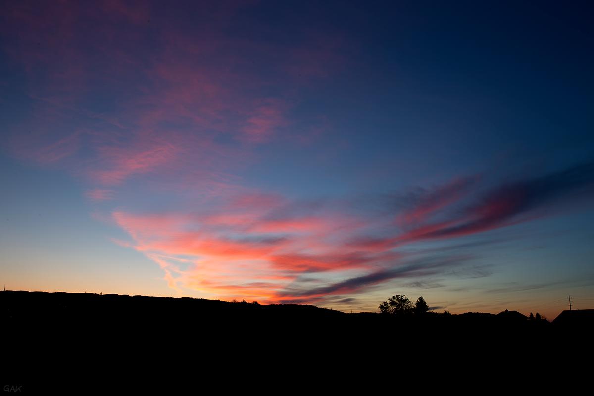 Sonnenuntergang – Unten im Bild die im dunkeln liegende Landschaft, darüber der blauschwarze Himmel mit rotorangen Wolken.