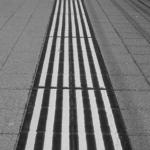 Schwarz-Weiss-Foto. Bahnsteig mit erhöhten Sicherheitslinien. Die Linien ziehen sich von unten nach oben durchs Bild.