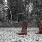 Ein paar braune Lederstiefel, die wirken als würde sie von links nach rechts durchs Bild gehen. Die Stiefel stehen auf einem Kiesplatz, im Hintergrund ist noch der Wald zu erkennen, beides in schwarz-weiss.