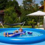 Ein Mann mit Hut, Sonnenbrille und einem Bier auf einer Luftmatratze liegend im Pool. Neben ihm schwimmt ein Grill mit einer Bratwurst und ein paar Bierflaschen. Im Hintergrund sieht man eine Hängematte, einen Sonnenschirm, eine Palme und Geranien.