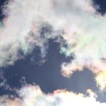 Weisse Wolken mit Ränder in Regenbogenfarben vor dem Blauen Himmel