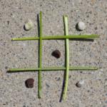 Der Hintergrund ist eine Steinplatte. Ein Tic Tac Toe Feld aus grünen Blumenstielen liegt darauf. Links davon Ligen die weissen, rechts die roten Kieselsteine. Ein paar Kieselsteine liegen schon auf dem Spielfeld.