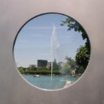 Ein rundes Fenster mit silbrigem Rahmen. Dadurch sieht man einen See, ein Springbrunnen, ein Boot, einige Bäume und Häuser.