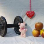 Von links nach rechts, eine Hantel, ein rosa Stoffschweinchen, ein rotes Herz mit weissen Punkten und drei Äpfel.
