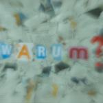 Eine Collage aus Zeitungspapier, in der Mitte kann man in grossen Buchstaben «WARUM?» lesen.