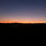 Ein Sonnenuntergang, der Himmel ist Blau-Rot gefärbt, die Landschaft liegt im Dunkeln.