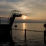 Ein Sprungturm am See. Im Hintergrund ist andere Ufer und die Sonne die durch die Wolken leuchtet.