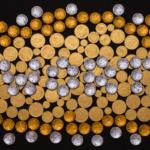 Der Hintergrund ist schwarz, darauf liegen viele goldene Schokoladenmünzen und Taler. In der Mitte steht «Wort» mit silbrigen Schokoladentaler.