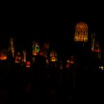 Bunte Laternen (Iffelen genannt), die an einem Umzug durch die dunkle Nacht getragen werden. Die Träger kann man im Dunkeln nur knapp erahnen.