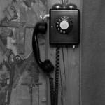 Das Bild ist scharz-weiss. Es ist ein Wandtelefon mit Wählscheibe abgebildet.