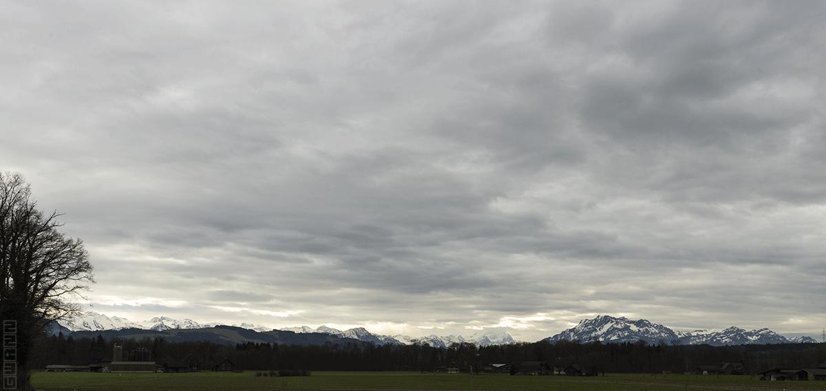 Das Bild zeigt eine Wolkenverhangen Berglandschaft. Man kann wenige Sonnenstrahlen erkennen.