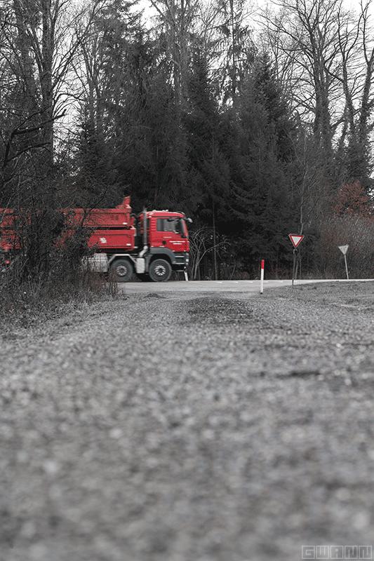 Im Vordergrund ist eine Kiesstrasse, im Hintergrund ein Waldstück. Auf der Strasse dazwischen fährt ein roter Lastwagen von links ins Bild.