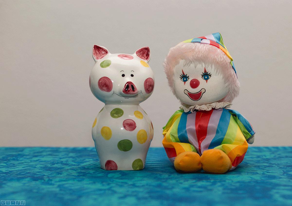 Auf dem blauen Untergrund steht ein weisses Sparschwein mit bunten Punkten und eine bunte Clown-Spieluhr.